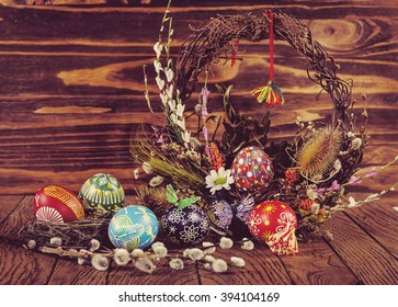 Easter eggs in the nest, decorative butterfly, flowers and blooming willow on the wooden background. Easter decoration. Happy Easter Instagram toning effect