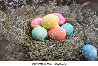 Easter eggs in a nest of grass and flowers.