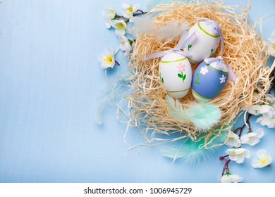 Easter eggs in nest on color wooden background. Easter still life with flowers, nest, feathers and eggs.