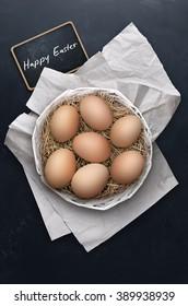 Easter eggs in nest on dark background.