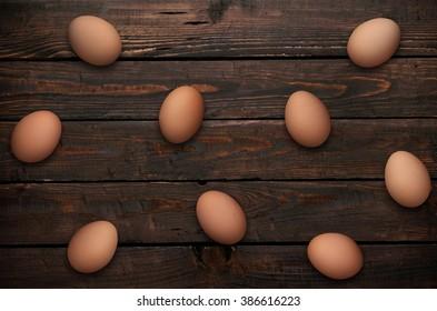 Easter eggs in nest on wooden background.