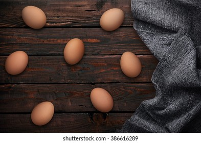 Easter eggs in nest on wooden background with drapery