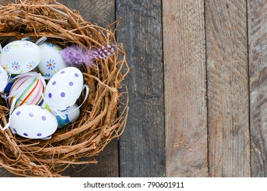 Easter eggs in nest on wooden background - Shutterstock ID 790601911