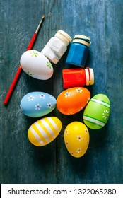 Easter eggs next to paints and brush