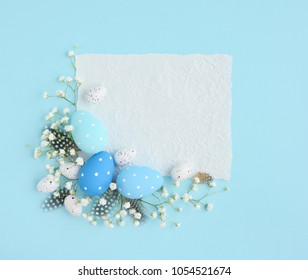 Easter eggs on a blue background. View from above, a piece of paper with space for text. Easter card