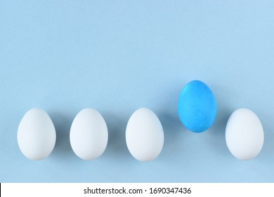 Easter eggs on a blue background. A row of white eggs and one blue.