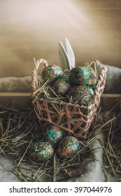 Easter eggs on rustic background with straw, textiles and baskets and hidden Bunny ears