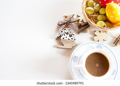 Easter eggs on the straw in a basket and wooden bunny and a cup of coffee on a white table. Easter decorations.