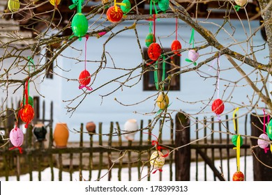 Easter eggs on a tree in front of wooden cottage. Slovakia.