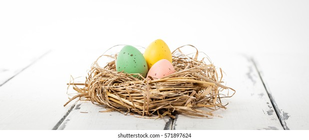 Easter eggs on white wooden horizontal banner
