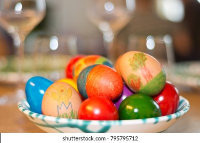 Easter eggs painted by children themselves in a fine Gmundner porcelain from Austria on a table set with wine glasses. (wide aperture, low depth of field)