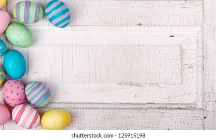 Easter eggs painted in pastel colors on a white cracked antique background