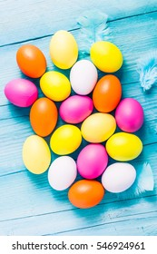Easter eggs in pastel colors on wooden table, from above