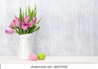 Easter eggs and pink tulips bouquet on shelf in front of wooden wall. View with copy space