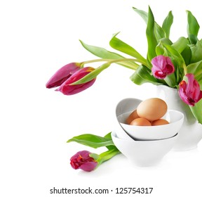 Easter eggs and pink tulips isolated on white