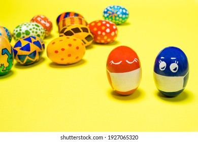 Easter eggs in protective masks on a yellow background - the Easter holiday during the coronavirus epidemic and quarantine. With painted eggs in the background