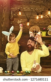 Easter Eggs - Recipes and Cooking. Father and kid painting Easter eggs. Rabbit's family with bunny ears. Cute little child boy wearing on Easter day.