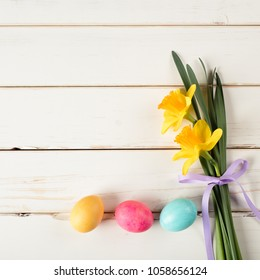 Easter Eggs in a Row on Bottom with Daffodil Flowers on the side of White Shiplap Board Background with room or space in center for copy, text, words or design.  A Horizontal photo with flat layout