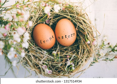 "Easter eggs with rubber stamp ""Frohe Ostern"" greeting text, Happy Easter in german, in a hay and flowers nest on a white wooden table"