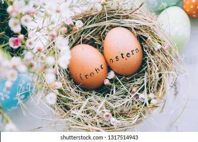 "Easter eggs with rubber stamp ""Frohe Ostern"" greeting text, Happy Easter in german, in a hay and flowers on a white wooden background"