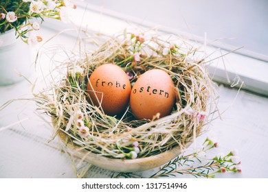 "Easter eggs with rubber stamp ""Frohe Ostern"" greeting text, Happy Easter in german, in a hay and flowers nest next to a window at home"
