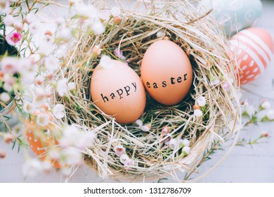 Easter eggs with rubber stamp Happy Easter greeting text in a hay and flowers nest on a white wooden background