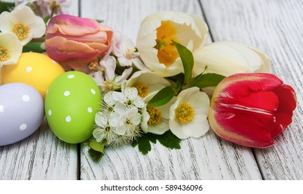Easter eggs and spring blossom on a old wooden background