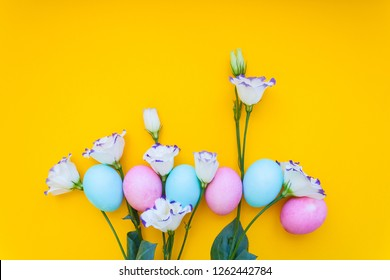 Easter eggs and spring flowers narcissi on yellow background
