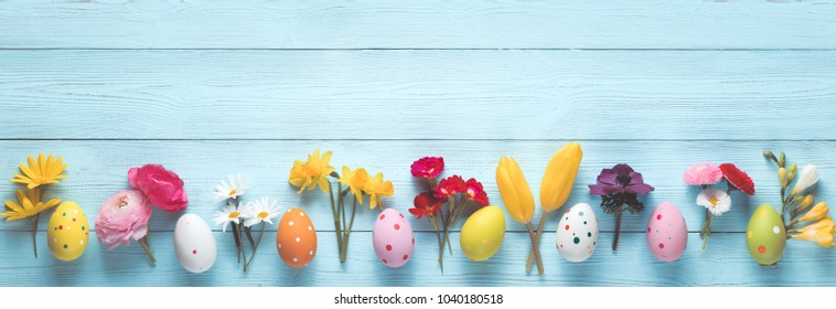 Easter eggs and spring flowers on wood