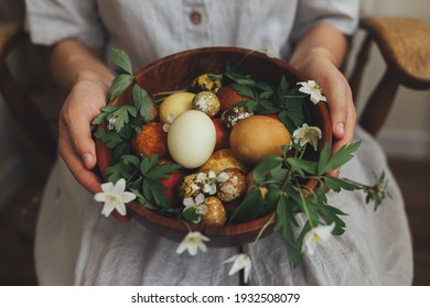 Easter eggs and spring flowers in wooden bowl in hands on background of woman in rustic linen dress. Stylish easter and quail eggs in natural dye and spring blooms. Aesthetic holiday - Shutterstock ID 1932508079