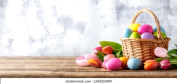 Easter eggs and tulip flower on wooden table