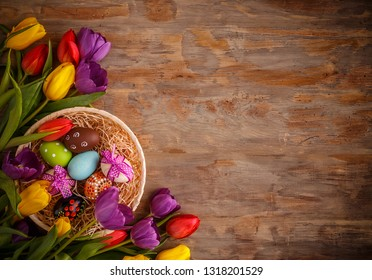 Easter eggs and tulips on old wooden background. View from above with copy space