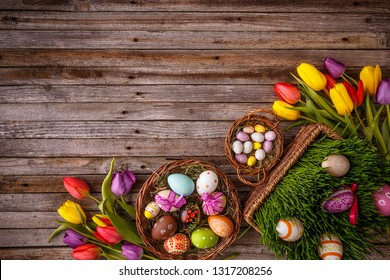 Easter eggs and tulips on wooden planks with space for your text