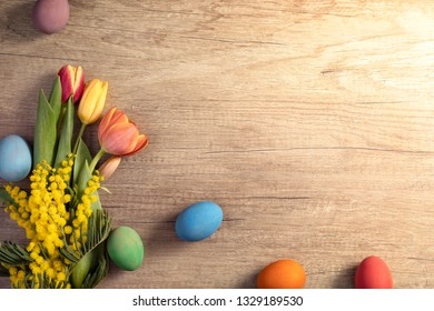 Easter eggs with tulips on wooden board, Easter holiday concept. Copy space for text.