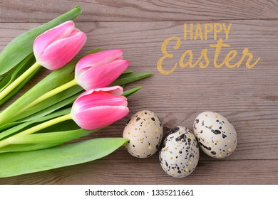 Easter eggs and tulips on wooden table. Festive decoration. Gold - Happy Easter!