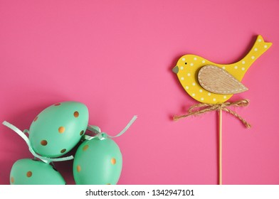 Easter eggs are white blue polka dots. Festive mood. Easter attributes. Drawing on the eggs. Pink background. Easter yellow bird topper.