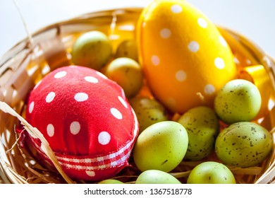 Easter eggs. White polka dots and green eggs in a little straw basket.