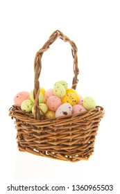 Easter eggs in wicker basket isolated over white background