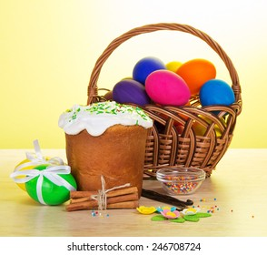 Easter eggs in wicker basket with napkin and Easter cake on green background