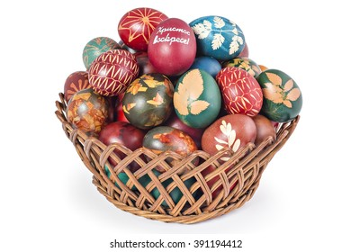 Easter eggs in woven basket isolated on white background