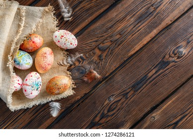 Easter eggs wrapped in canvas fabric on dark wooden background