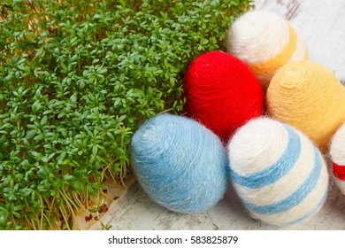 Easter Eggs Wrapped Woolen String And Green Cuckooflower Cress On Old Wooden Background Decoration For