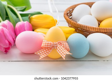 Easter eggs with yellow tulips on a white wooden table