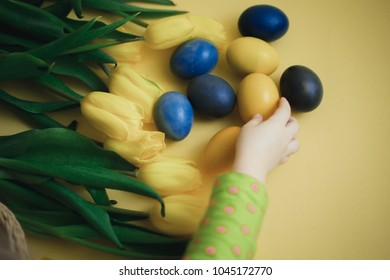 The Easter eggs with yellow tulips on yellow background. Child hand