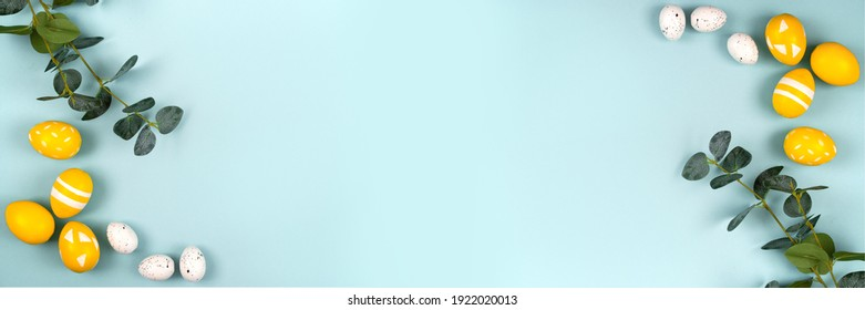Easter eggs in yellow and white colors and a branch of eucalyptus on a pastel blue background. Flat lay, top view. Banner