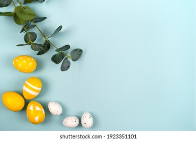 Easter eggs in yellow and white colors and a branch of eucalyptus on a pastel blue background. Flat lay, top view.