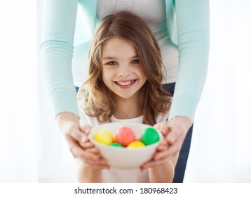 easter, family, holiday and child concept - smiling little girl and mother holding bowl with colored eggs