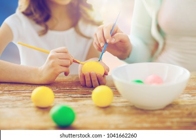 easter, family and holiday tradition concept - close up of happy little daughter and mother coloring eggs over sky background