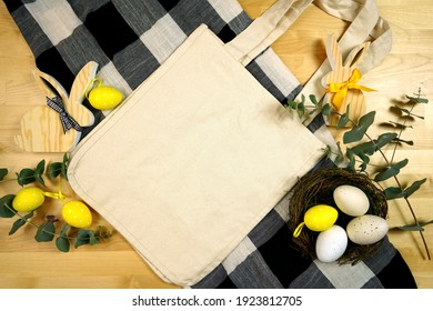 Easter Farmhouse theme product flatlay mockup with buffalo plaid and wood bunnies. Natural canvas cotton Easter Egg Hunt tote, shopping bag with negative copy space for your text or design here.