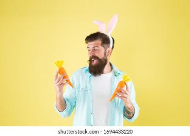 Easter fast. Easter rabbit man hold carrots. Happy hipster enjoy vegetarian food. Vegetarian diet. Vegan food. Vegetarian abstain. Healthy dieting and fasting. Spring vegetarian recipes.